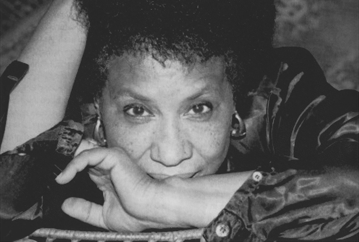 Close-up black and white photo of a woman with a medium-dark skin tone looking directly into the camera. Resting her head on a table, she crosses her left arm in front of her mouth, reaching her right hand up to her hair. She wears a dark blouse, open at the cuffs, gold hoop earrings.
