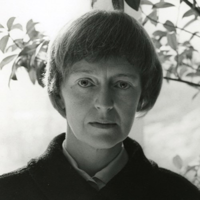 A black-and-white photograph of a light-skinned adult woman looking straight-on at the viewer. She sports a bowl cut with bangs cut significantly above her brow, and a collared shirt under a dark colored jacket. Behind her are delicate branches with leaves.