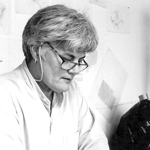 Black and white photo of a middle-aged woman with short grey hair and light skin. She sits against a wall and looks down, her glasses sliding down her nose slightly. She has an expression of concentration, as if she is focusing on something in her hands.