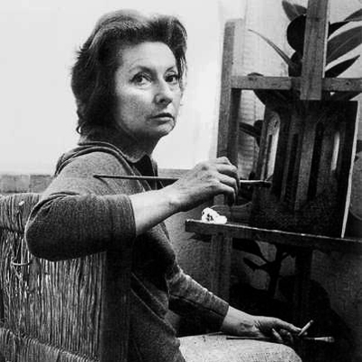 A black-and-white photograph of Remedios Varos, seated in front of an easel. She turns from an easel to face the camera, cigarette in her left hand and paintbrush in her right. Her brushed-back dark hair frames her light-skinned face, falling to just below her chin.