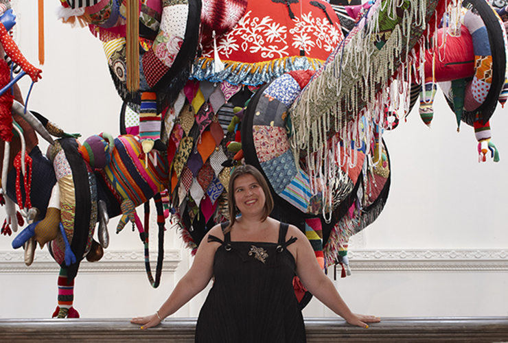 A light-skinned adult woman with bobbed brown hair wears a black sleeveless dress. She smiles wide and leans her hands back against a railing. Behind her is the lower portion of a large colorful fabric sculpture in front of a white wall.