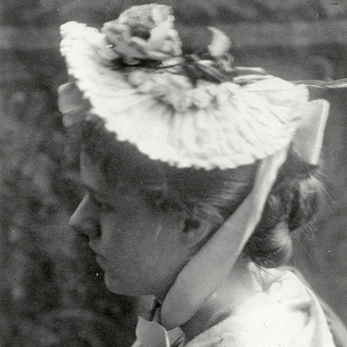 A soft-focused black-and-white photograph of a young light-skinned woman. She is in profile, and her light-colored hair is pulled into a bun. She wears a ruffled hat, with a sash tied under her chin. She is positioned in profile looking to the left of the image.