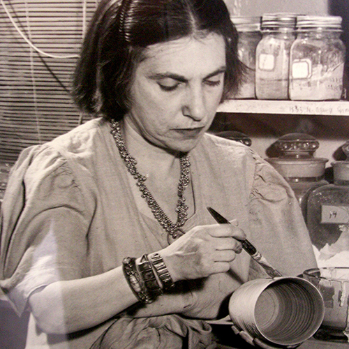 A black-and-white photograph of a light-skinned adult woman with short dark hair pinned away from her face. She brushes glaze onto a vase-shaped ceramic vessel in her other hand. She wears a smock-like dress, thick bracelets, and a necklace. Behind her are labeled mason jars.
