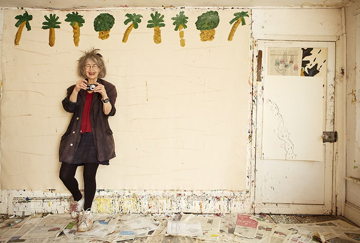 Color photograph of a light-skinned woman with grey hair holding a small digital camera. She stands in a delapidated room that has simple palm trees and pineapples painted at the top of one wall. Smiling, she wears white sneakers and props one foot up against the wall.
