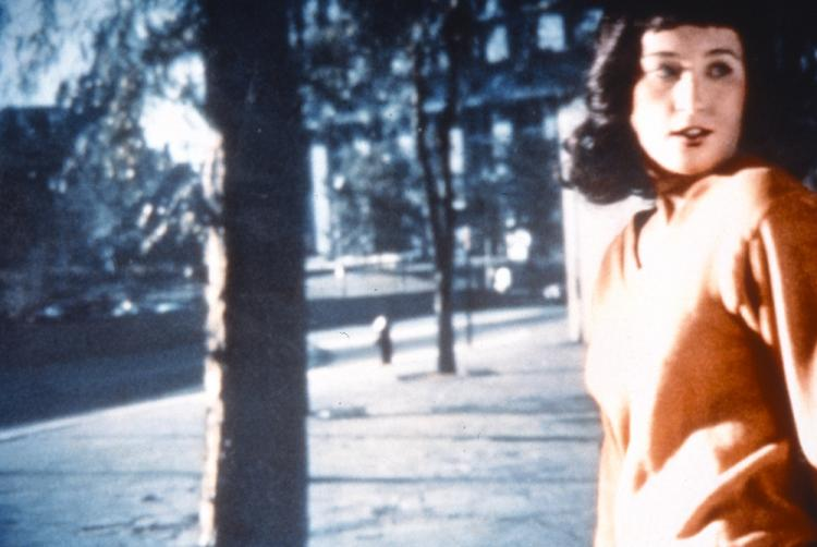 A woman stands in an orange sweater, her body turned to the center while she looks over her left shoulder, her mouth slightly open. Her dark hair is shoulder-length and contrasts with her light skin. Behind her, a screen with the image of trees and a building projected onto it.