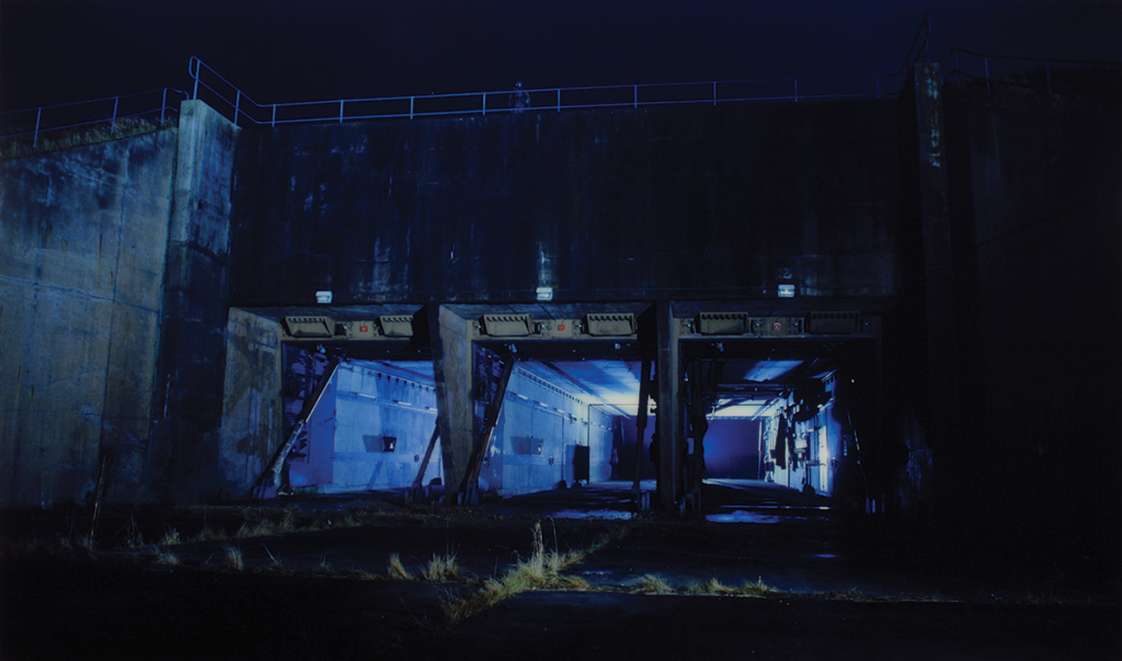This photograph documents an abandoned military structure at Greenham Common, a former Royal Air Force station in Berkshire, England. Once a site conveying military strength, the scene captured by the artists offers a different perspective—one of decay and abandonment. The photograph's otherworldly glow highlights the empty interior of the space.
