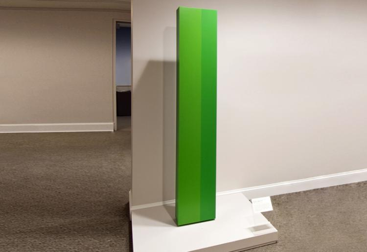 Tall, rectangular, pillar-like sculpture, painted in vibrant green hues on a smooth, clean surface.