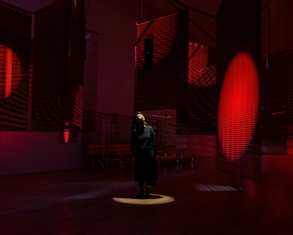 Artist Haegue Yang stands in a spotlight in the middle of her immersive exhibition, in a room with red lighting, and big banner-like structures hung from the ceiling. She looks up at one of the structures that has a red circle of light projected on it.