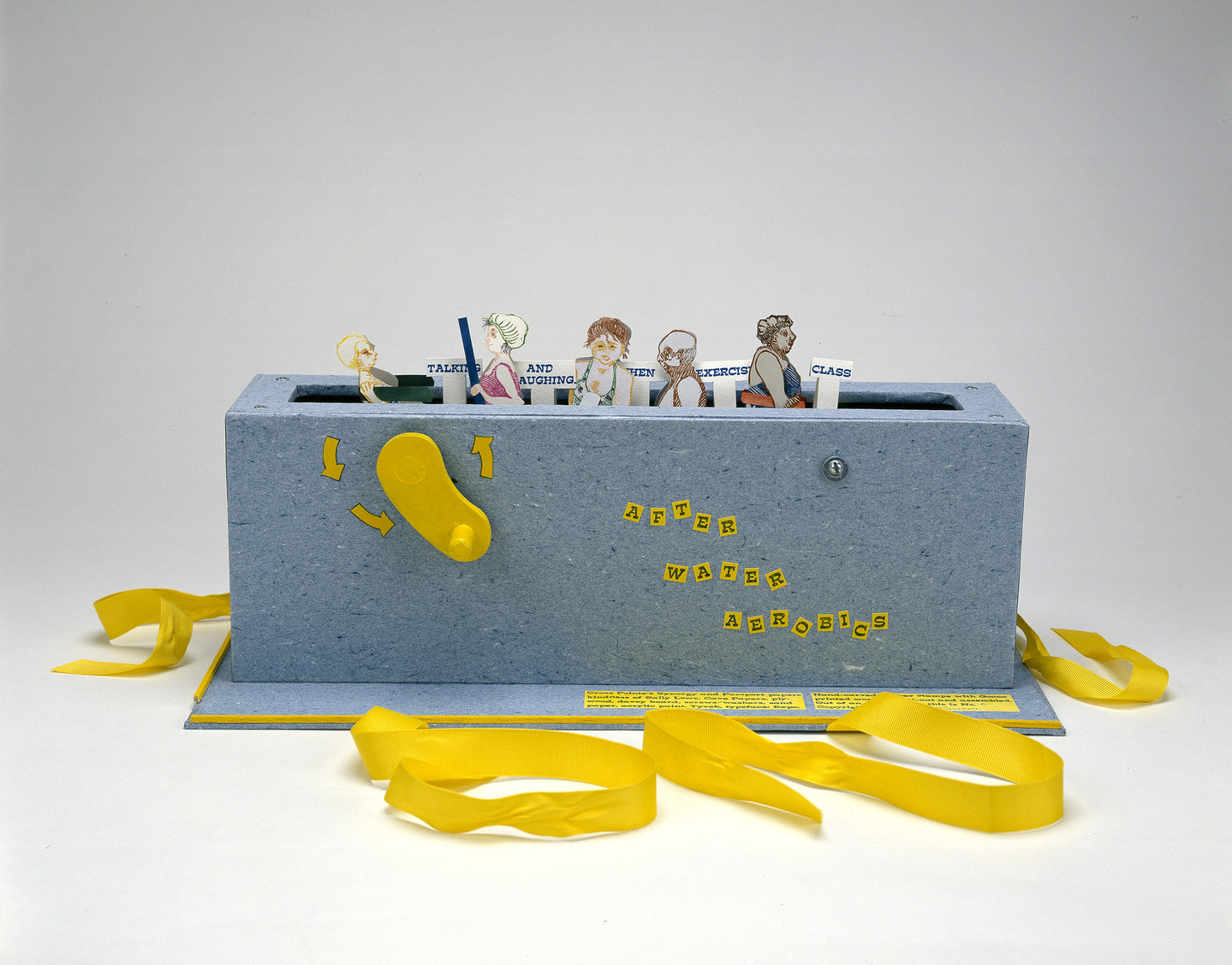 "Paper figures in swimwear emerge from a grey-blue box with a slot in the top, like a toaster, and a yellow crank on the side. Small signs say ""talking"" ""and laughing"" ""exercise"" ""class."" Yellow ribbons, untied, are at the base of the box."