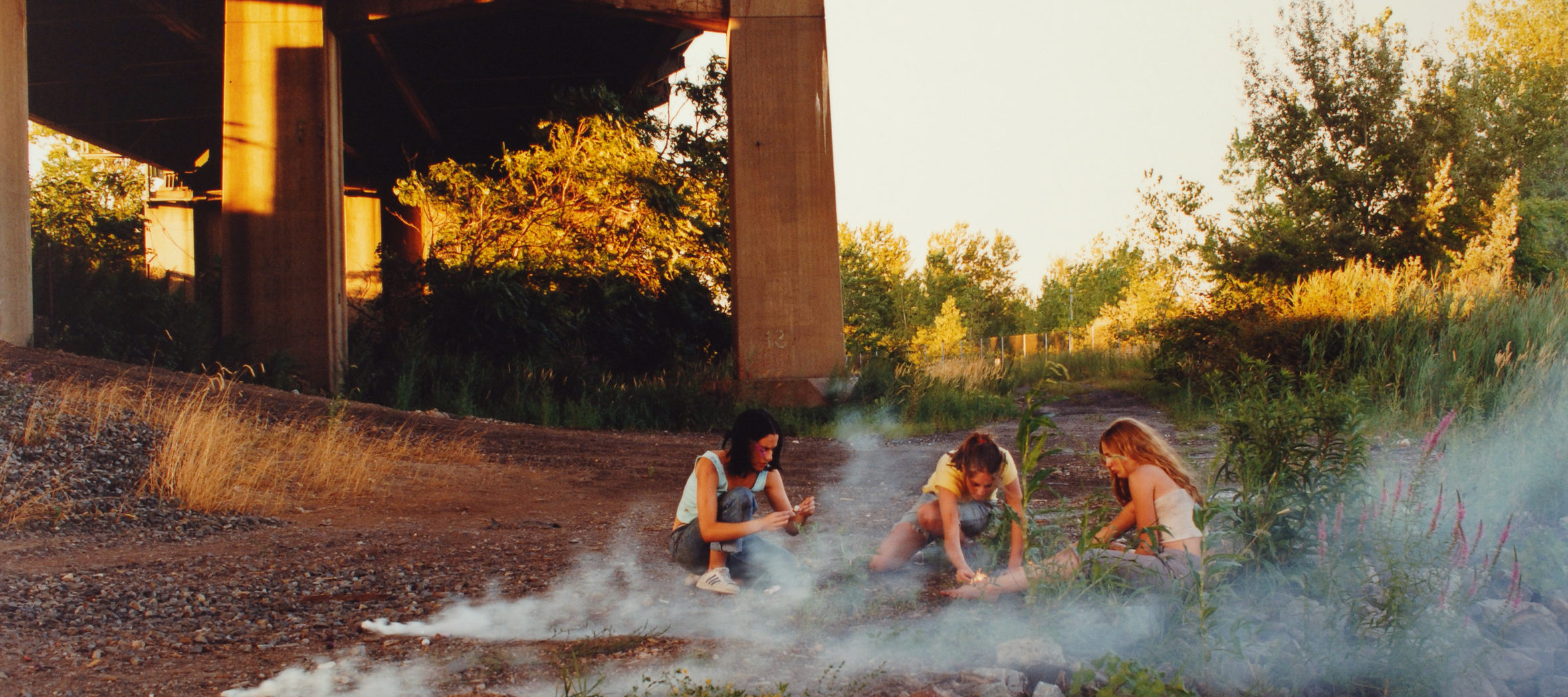Crouching in the shadow of a highway overpass, three teenage girls with light skin focus intently on lighting smoke bombs.