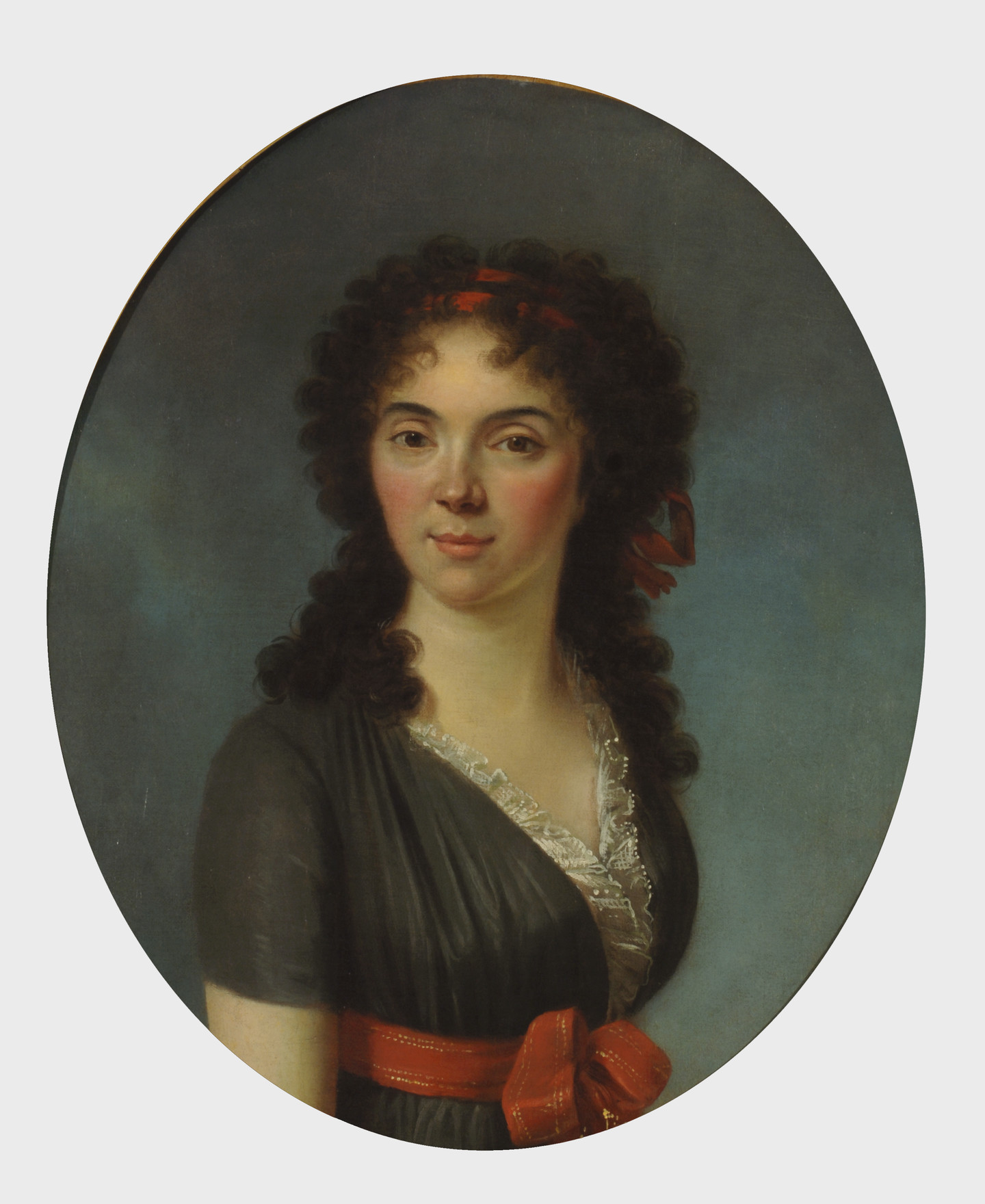 Oval portrait of a young woman with light skin gazes out at the viewer with her dark tousled curls framing her face and shoulders.