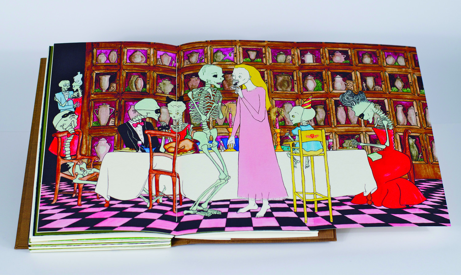 The open page of a book depicts a dinner party, attended by well-dressed skeletons, set in front of shelves of urns. In the foreground, a blonde woman wears a long, pink dress and sips red wine, engaging in conversation with a skeleton.