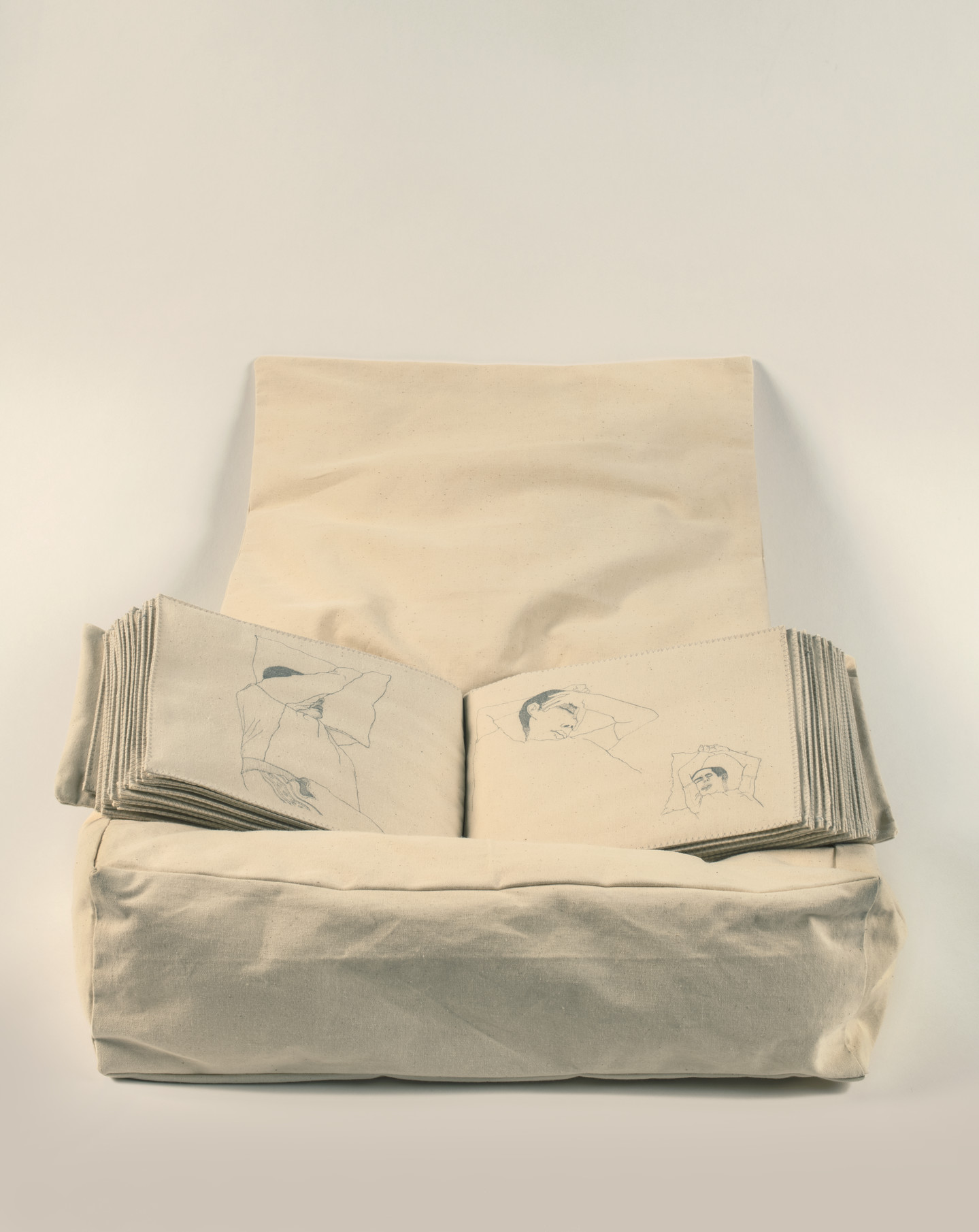 A stuffed, pillow-like box in beige holds an illustrated book with fabric pages. Three drawings of people sleeping fill the open book.