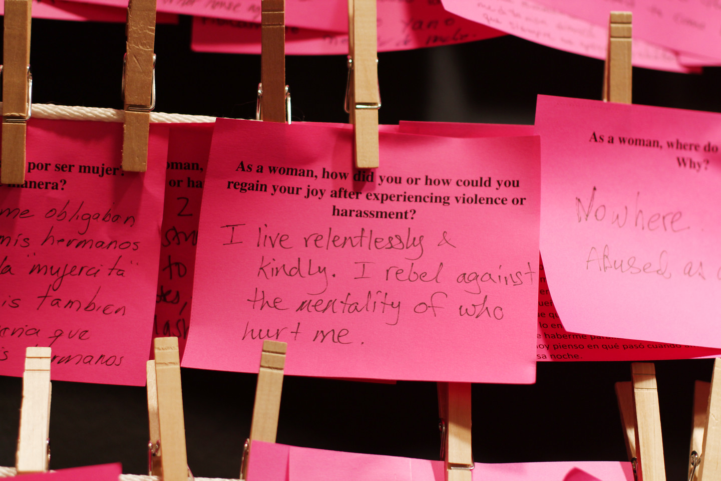 Multiple pink post-it notes hung on a clothesline with clothespins. There is a handwritten note in response to a typed question about regaining joy. The response is