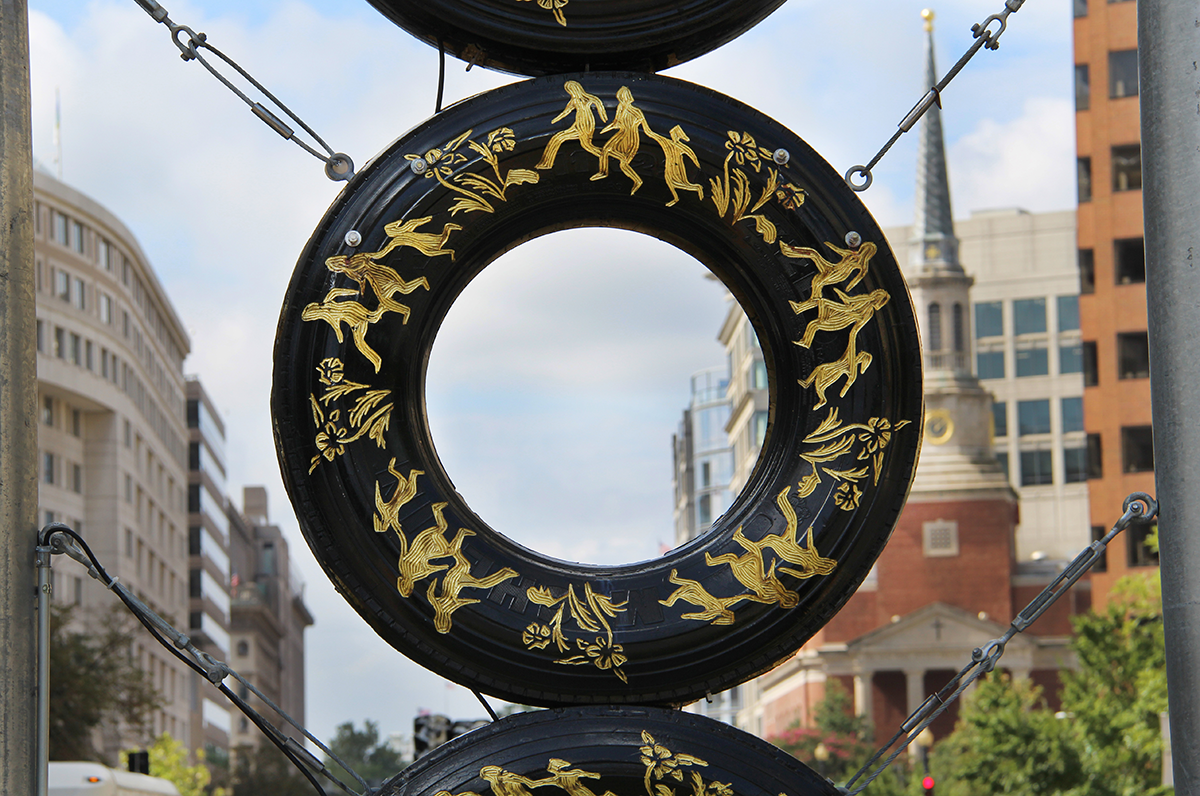 "Detail of Bestabee Romero's ""Signals of a Long Road Together"" installation on New York Avenue in Washington, D.C; this tire shows an image of a family fleeing on foot and flowers, the images are carved into the tire and painted gold."