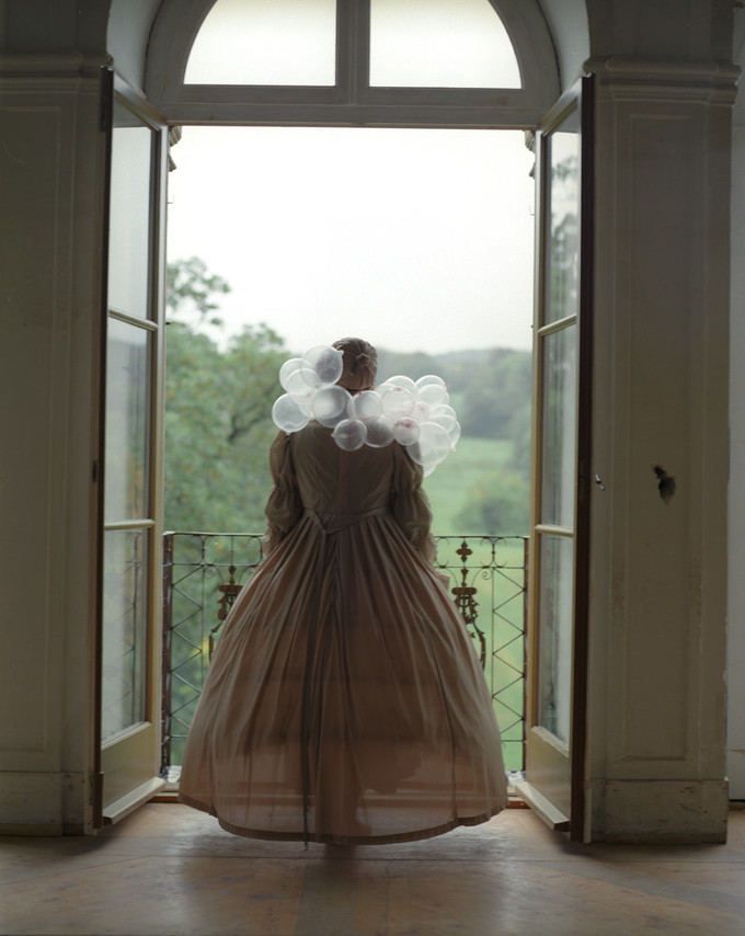 An adult woman seen from behind standing before two open glass doors leading out to a balcony overlooking greenery. She is dressed in a long, tan, period gown and her hair is tied up. Around her shoulders are several clear bubbles, resembling a scarf made of bubbles.