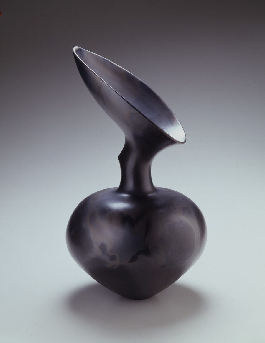 Black earthenware vase with bulb-shaped bottom, thin neck, and an angled funnel top.