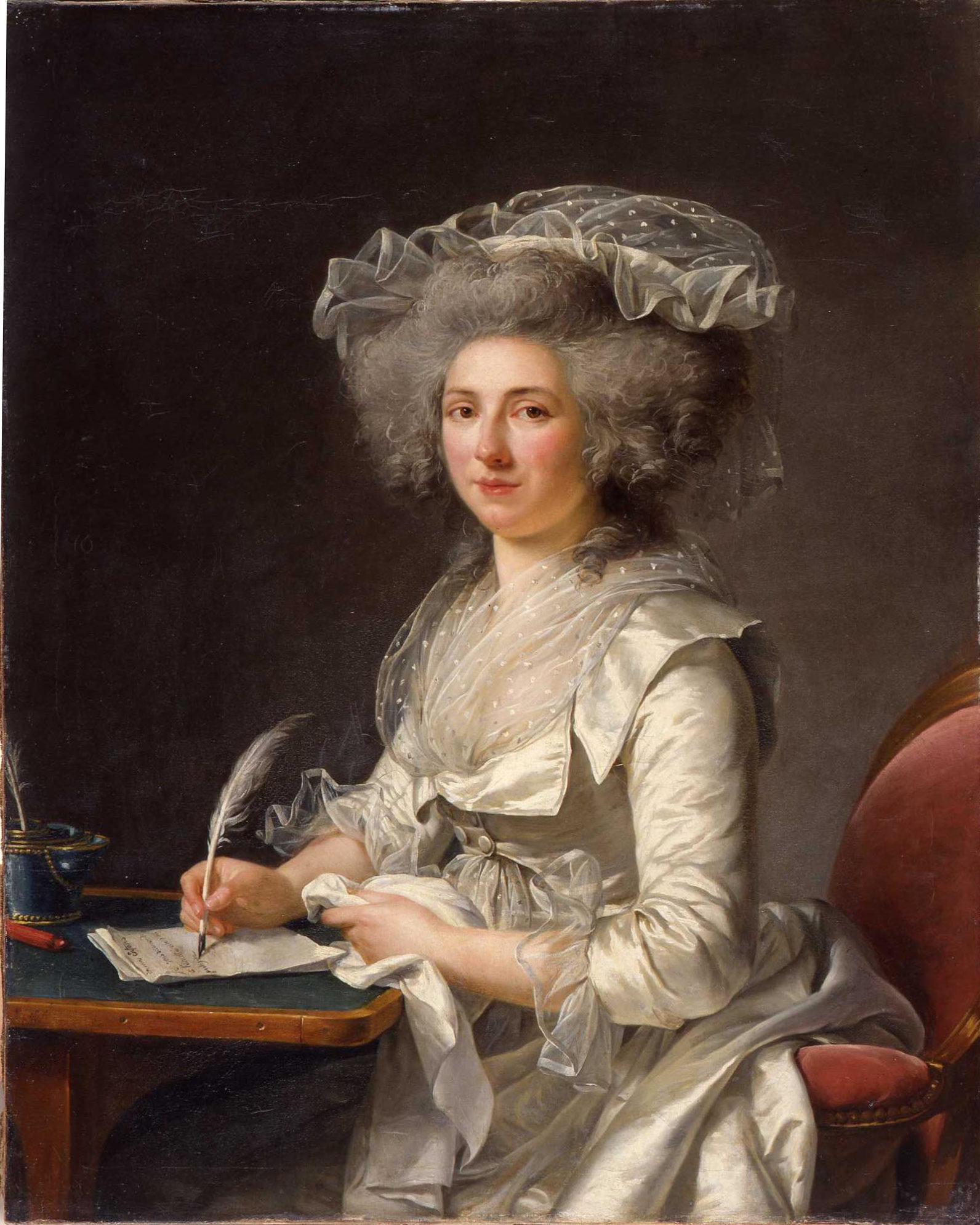 A portait of a woman dressed in fine ivory silks sitting at a writing desk grasping a feather quill pen in her right hand. She gazes out towards the viewer and her skin is a pale, pinkish hue, with a baroque hairstyle and tulle bonnet.