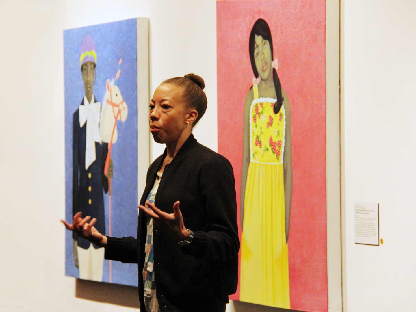 Amy Sherald speaks to a crowd in a gallery beside her striking portraits depicting individuals with gray skintones against vibrant, solid-colored backgrounds. She gestures with her hands and has a serious expression on her face.