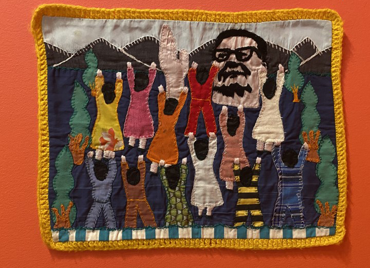 A small quilt-like textile features an image of former Chilean President Salvador Allende, whose government was overthrown by dictator Pinochet, over mountains with his hand in an upward motion. Eleven figures put their hands up in response as they stand among trees.