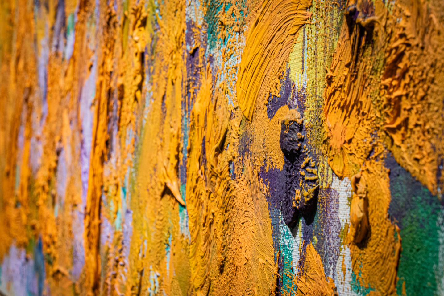 Close-up detail of an abstract painting with very thick and gestural brushstrokes of mostly orange paint.