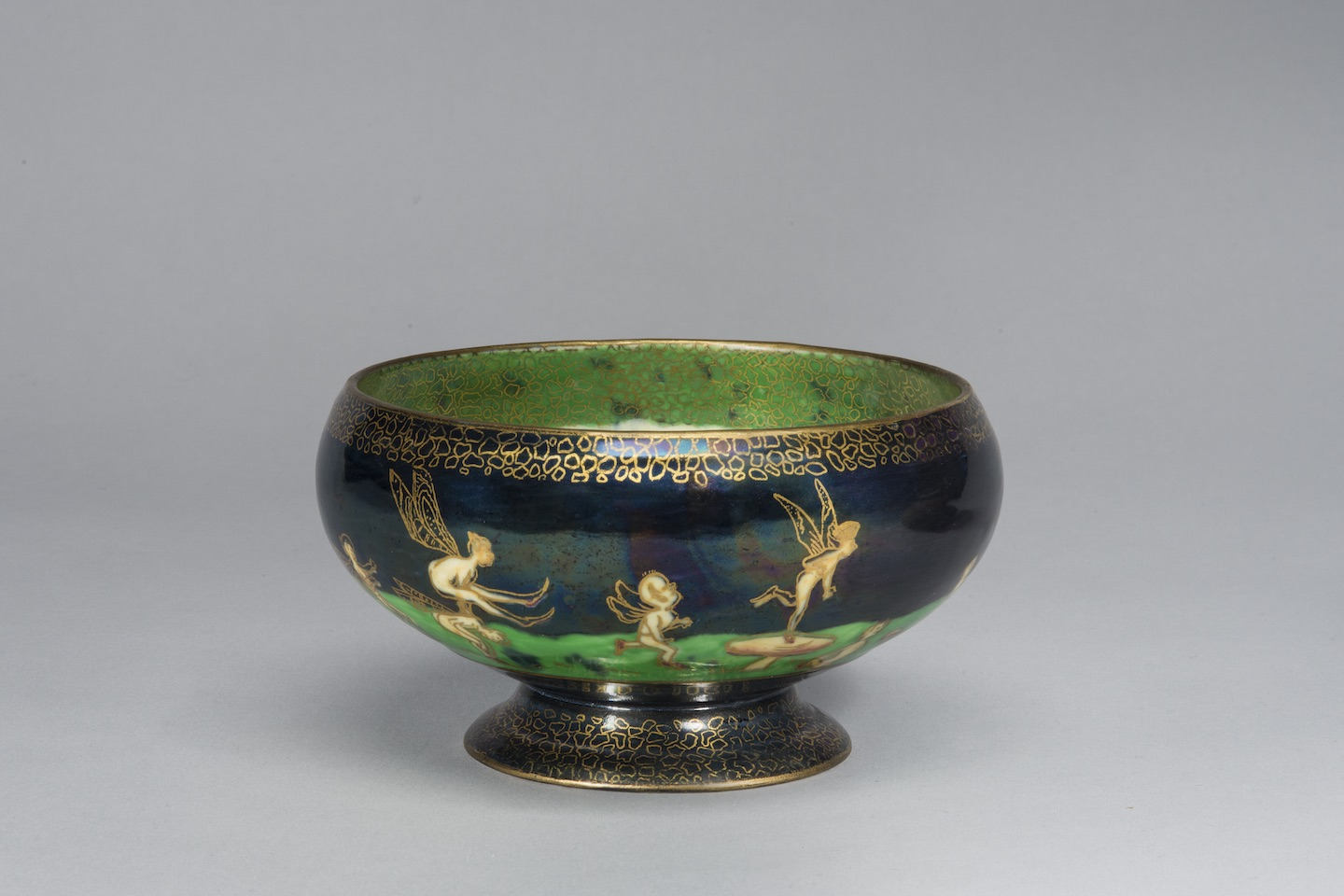 Porcelain pedestal bowl featuring an iridescent lustreware glaze. Around the bowl, winged fairies and sprites cavort on a vibrant green field set against a deep blue background. The figures and the decorative elements along the rim and foot of the bowl are outlined in gold cloisonne.