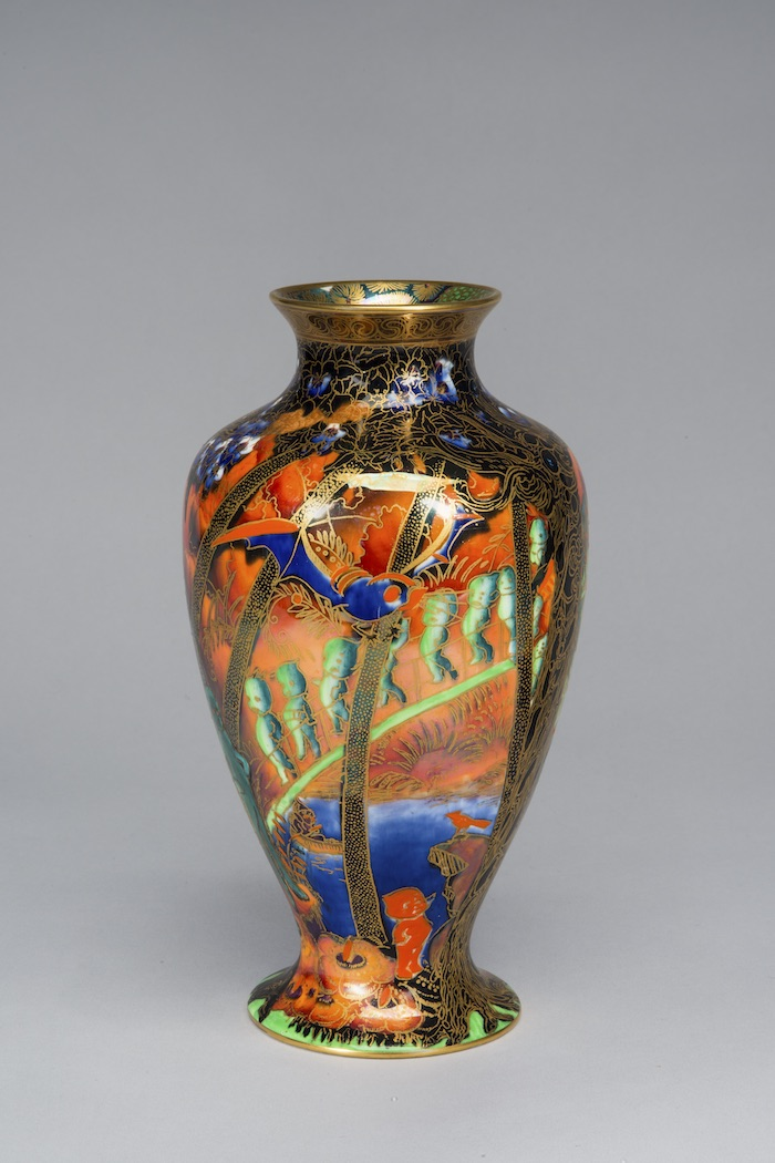 Iridescent lusterware vase features gold cloisonne and an ornamental Art Nouveau design. Against a vibrant orange background, the long twisted trunks of forest trees surround the vessel. A blue bat circles the treetops, while a procession of odd cherubic figures descends along a draping vine.