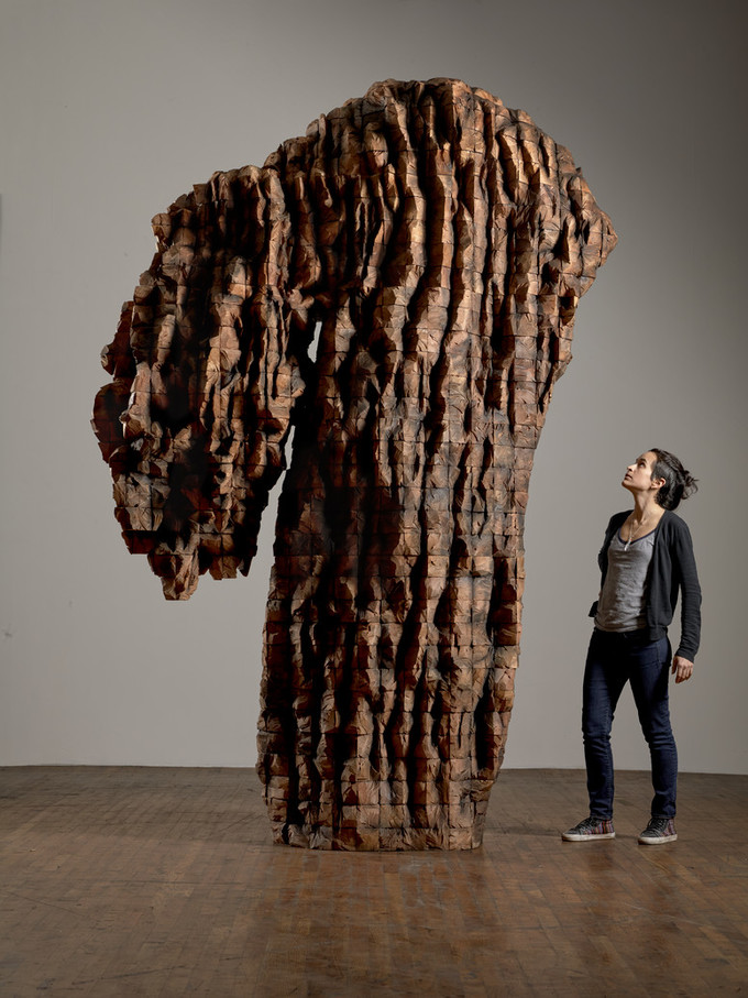 Female visitor with light skin looks up at a roughly 20 foot tall carved cedar sculpture.