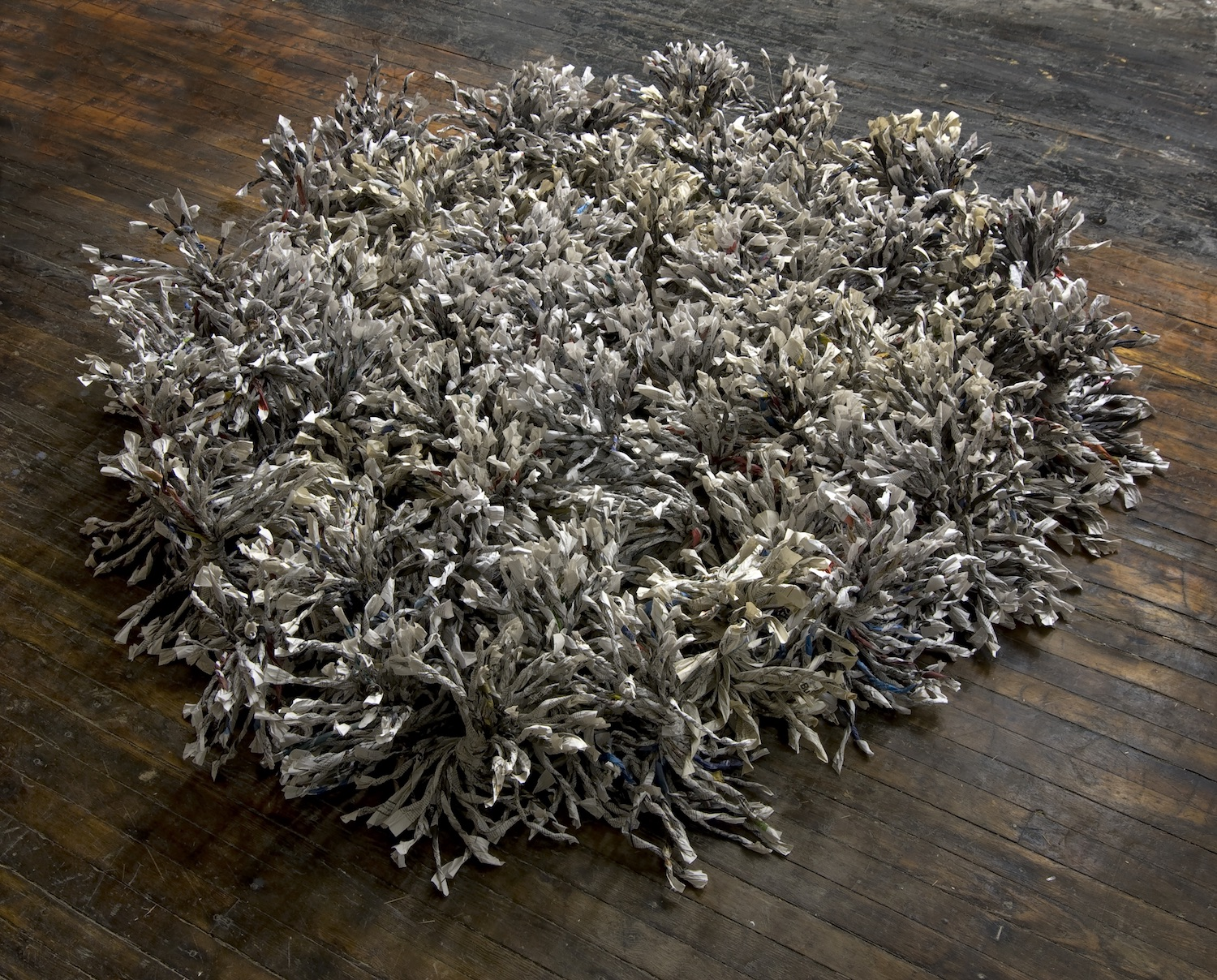 Six-square-diameter floor sculpture of shredded and twisted newspapers.