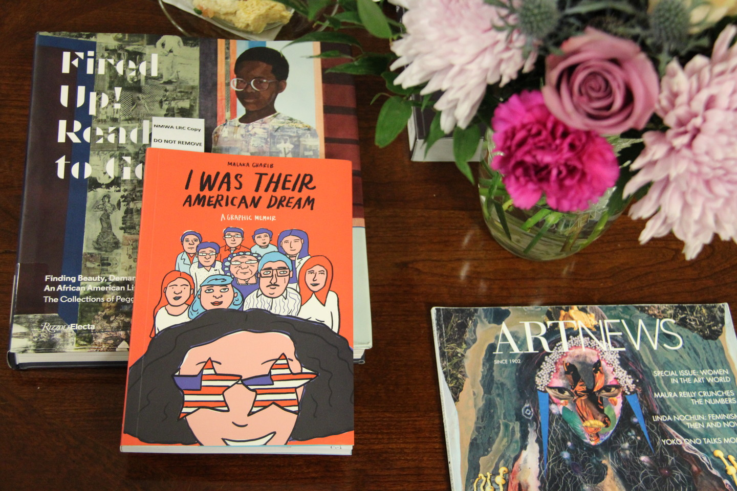 Two books, Fired Up! Ready to Go and I Was Their American Dream, rest on a tabletop, along with a small vase of pink and lavender flowers.