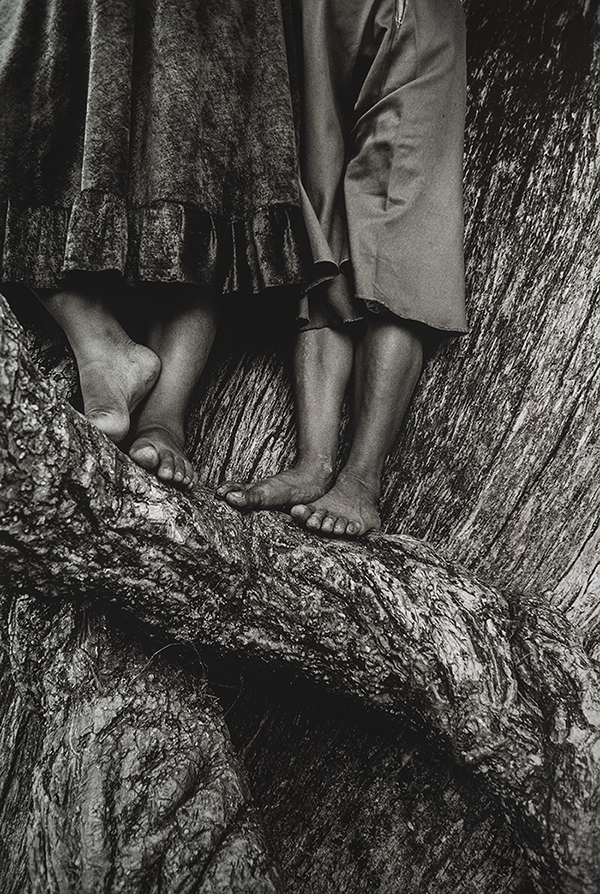 A black and white photo of two women's legs and feet standing in the grooves of an ancient tree. The photograph was taken at the popular pilgrimage site of Chalma in Mexico and evokes a religious experience.