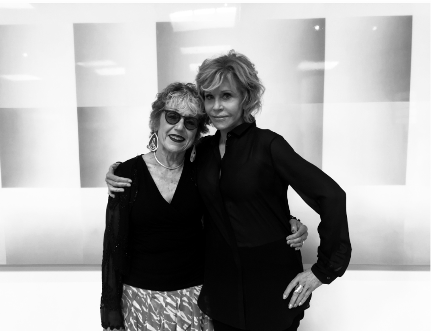 A black and white photo of Judy Chicago and Jane Fonda who pose with their arms around each other, smiling, in front of one of Chicago's paintings.