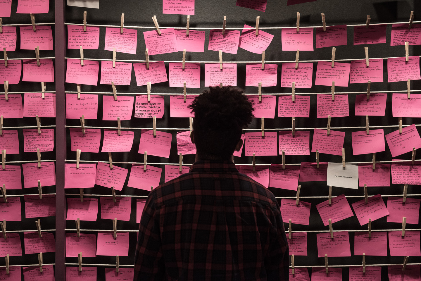 Man stands in front of rows of hot pink post-it notes.