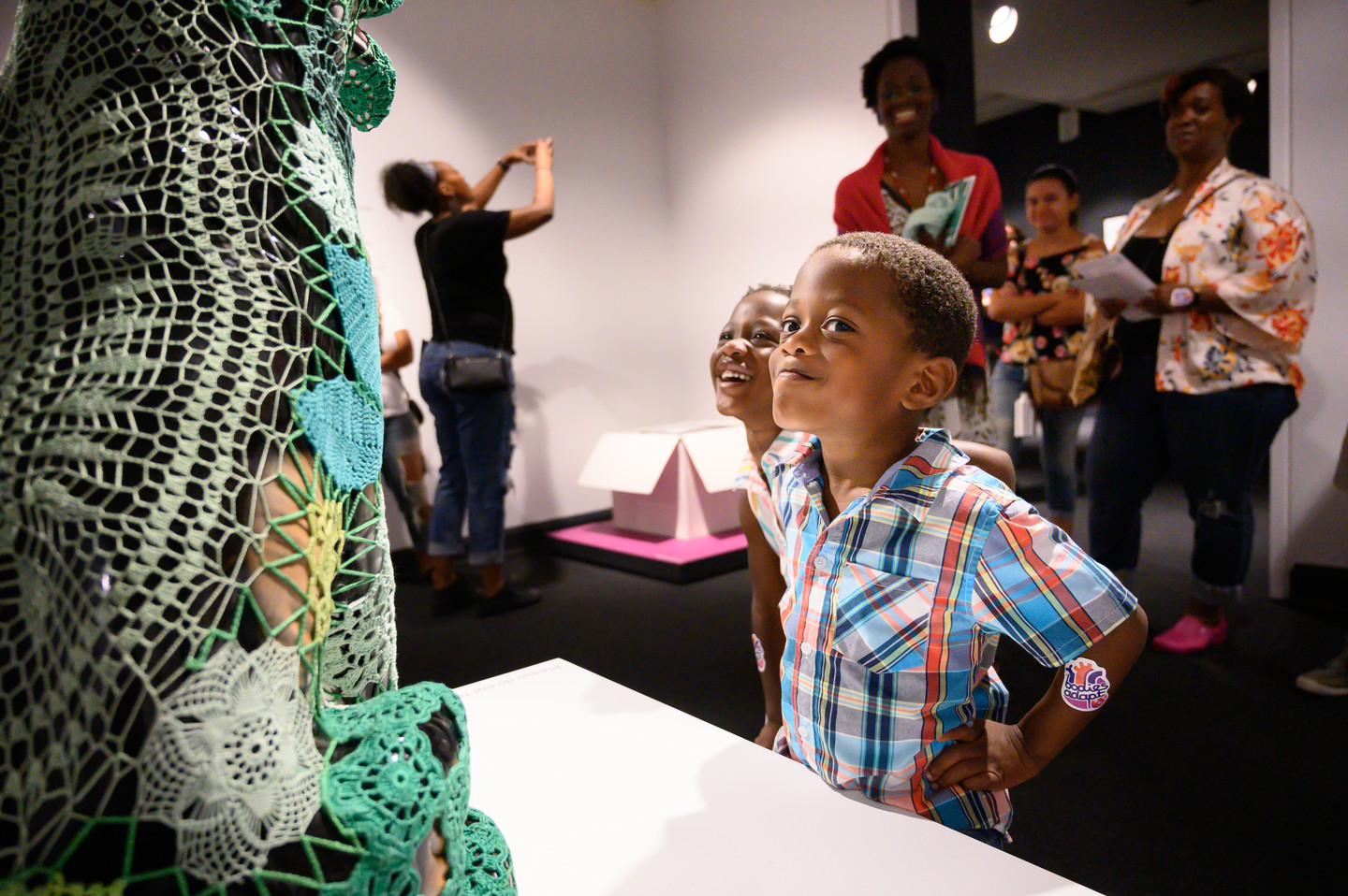 Two young children with medium skin tone stand in front of a dog sculpture covered with green crochet panels. One child stands with hands on hips, eyes turned to look directly at the viewer, and gives a slight smirk. Adult visitors in the background look at the scene with amusement.