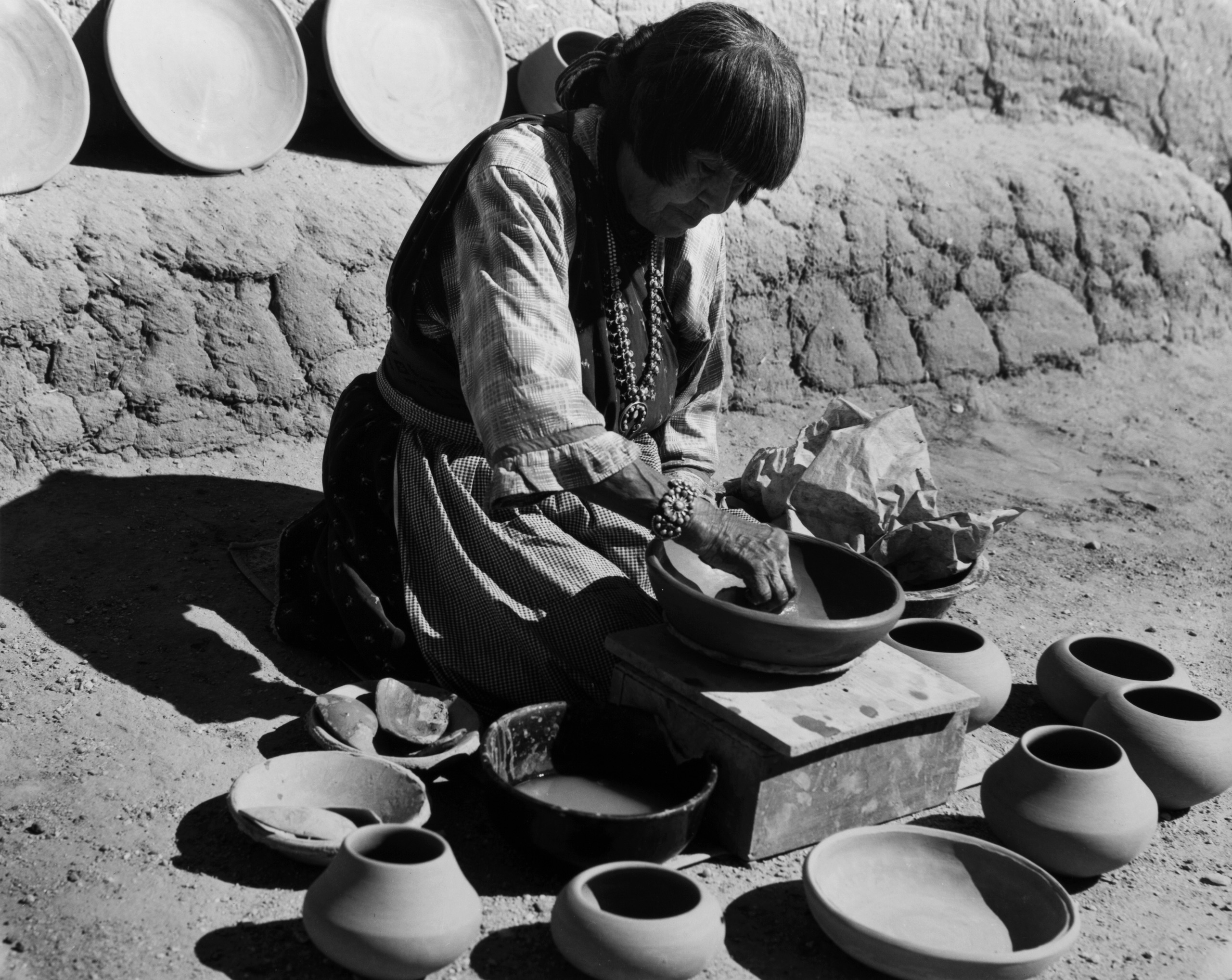 Black and white photograph of woman with medium skin tone making pottery.