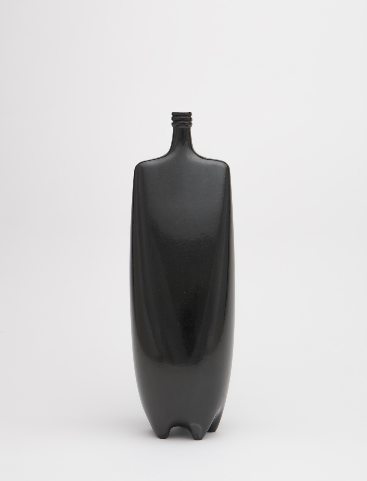 Shiny, black sculpture made of clay resembles a bottle with a square top and rounded body.