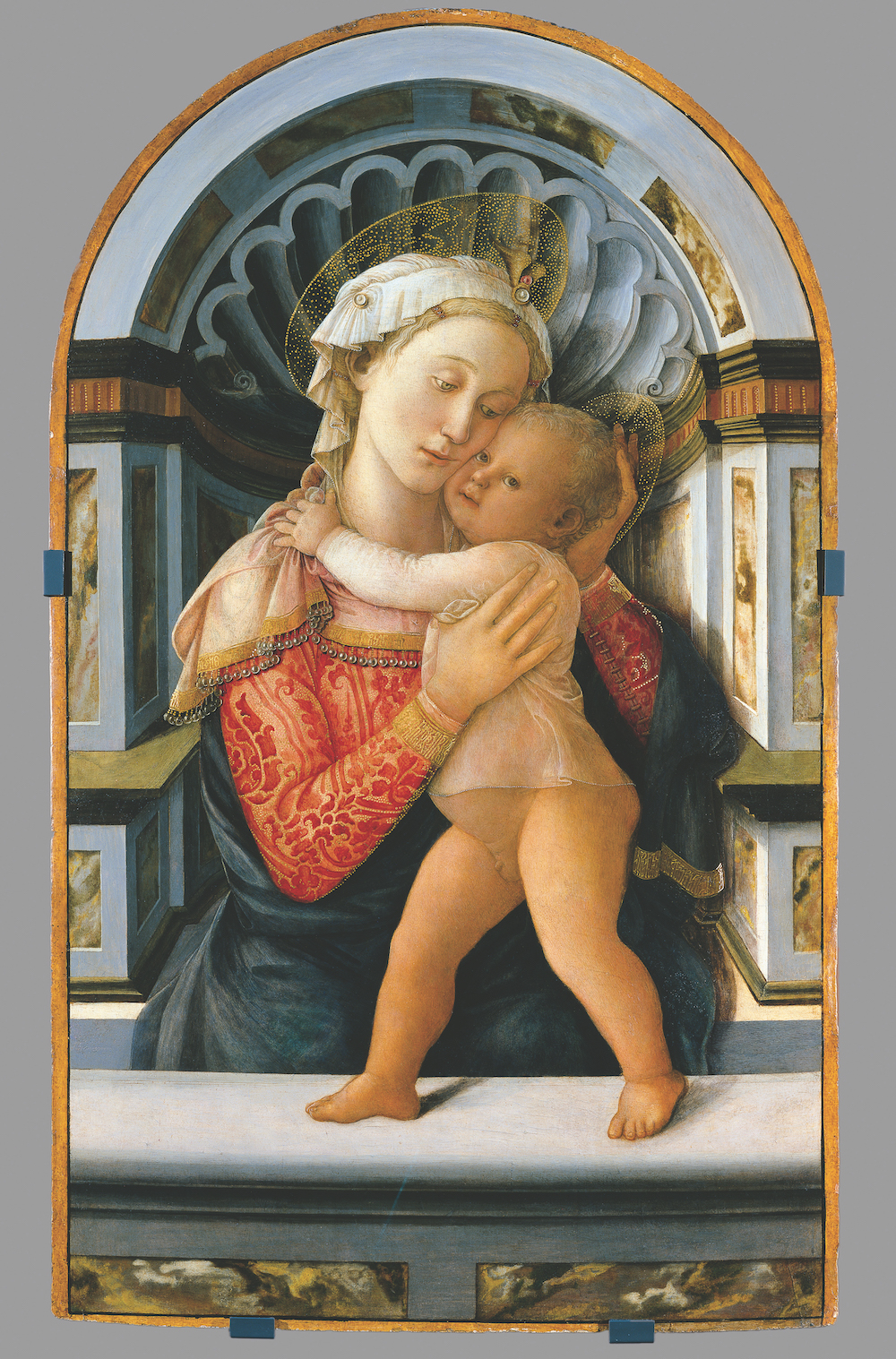 Early Renaissance style portrait depicting Mary and baby Jesus set against a Classical niche background. The image shows the faces of a light-skinned woman and baby, cheek-to-cheek in an embrace, with delicate golden halos framing their heads.