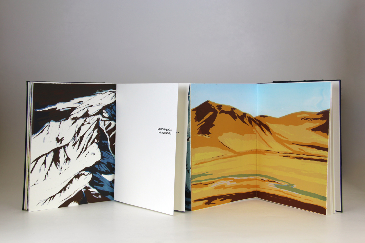 Four leaves of an open book depict mountain ranges. One image shows snow-capped mountains in blue, black and white; the other image depicts a low mountain in desert colors of beige, brown and yellow with a stream in the foreground.