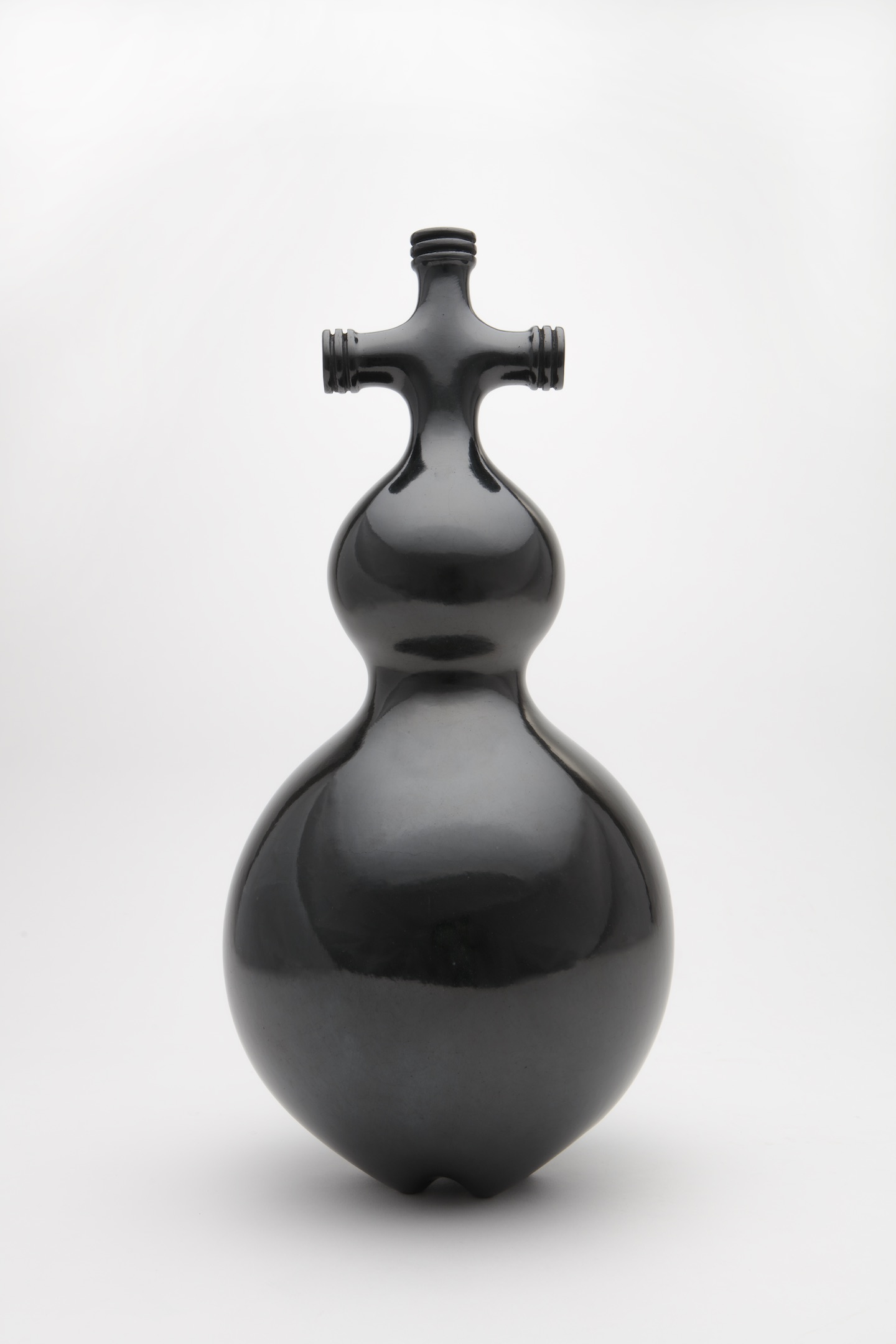 Black, shiny sculpture made of clay features a cross-like shape on top of two bulbs of increasing size.