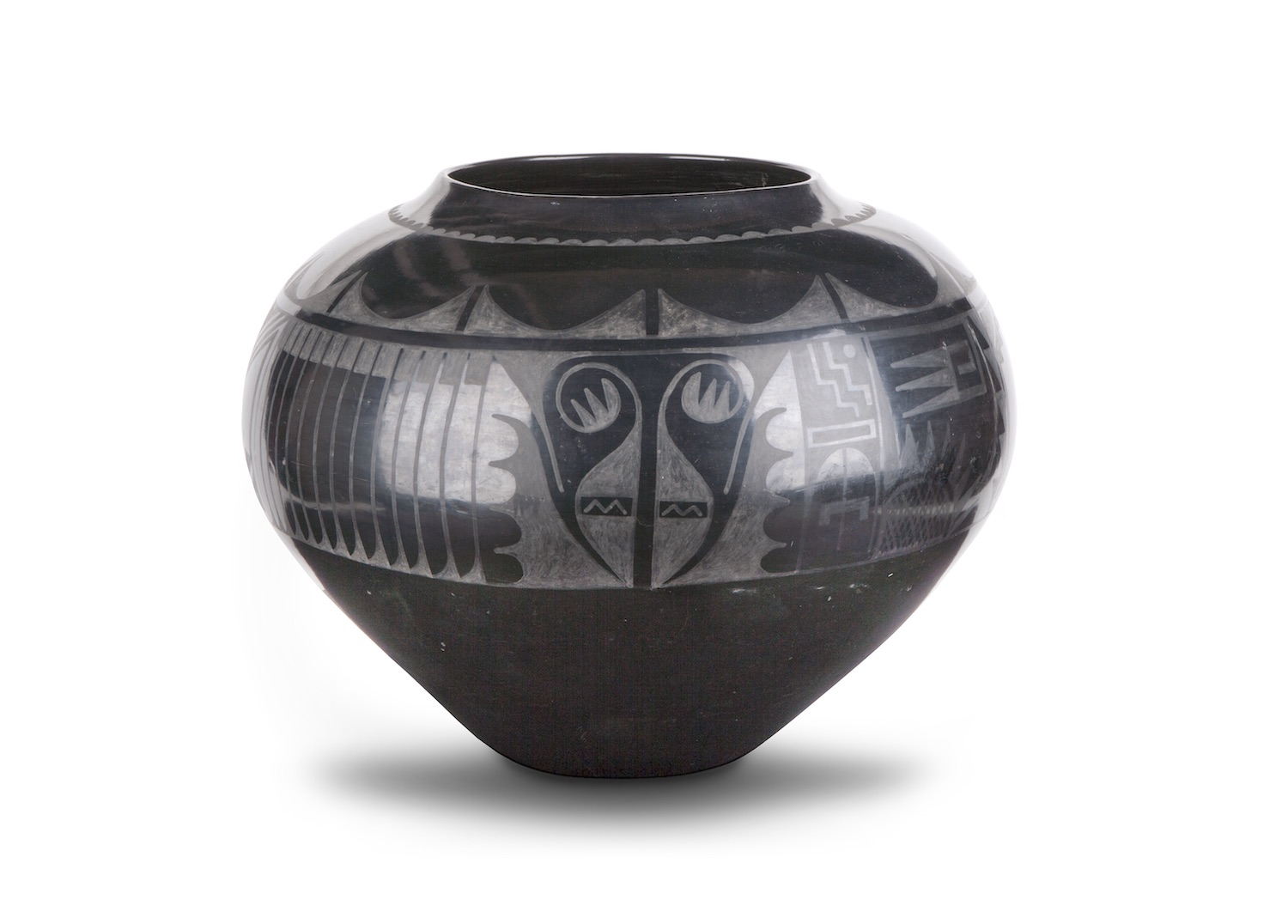 Blackware jar made of clay and volcanic ash. A painted, matte design adorns the upper half of the jar.