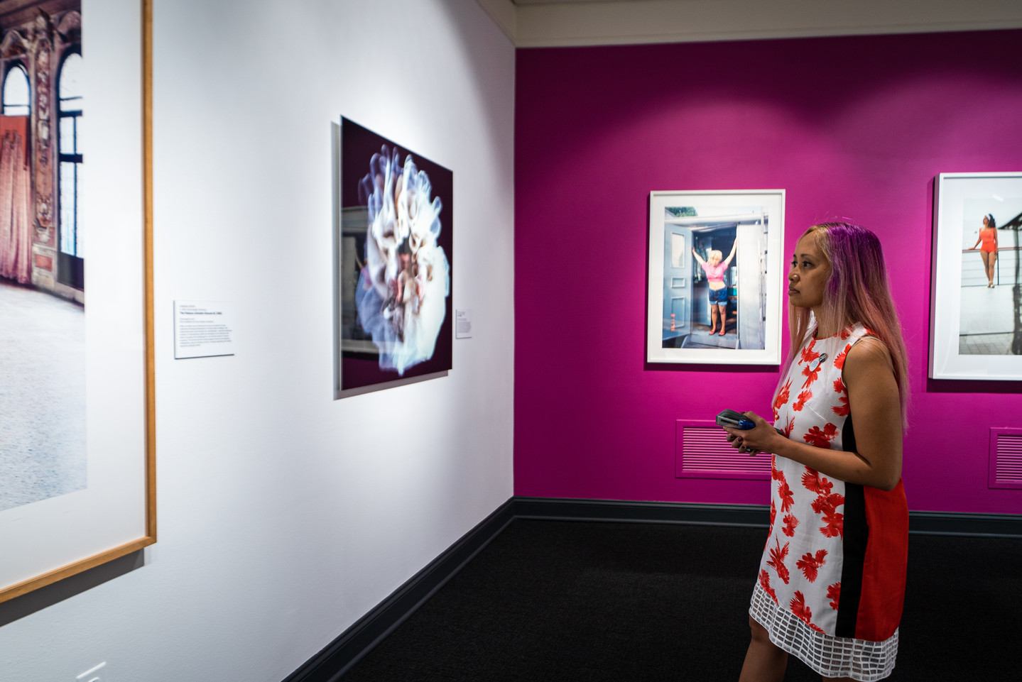 A women stands facing a white wall with two artworks. On the adjacent wall are two more artworks against a bright pink backdrop.