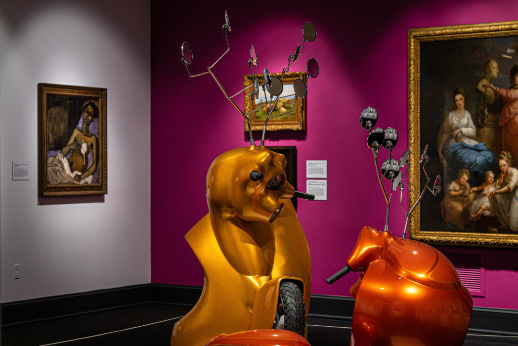 Gallery view with contemporary sculpture made of motorscooters that resemble two antlered animals fighting in foreground.Three paintings hang on a magenta wall in background. To the left on a white wall hangs another painting.