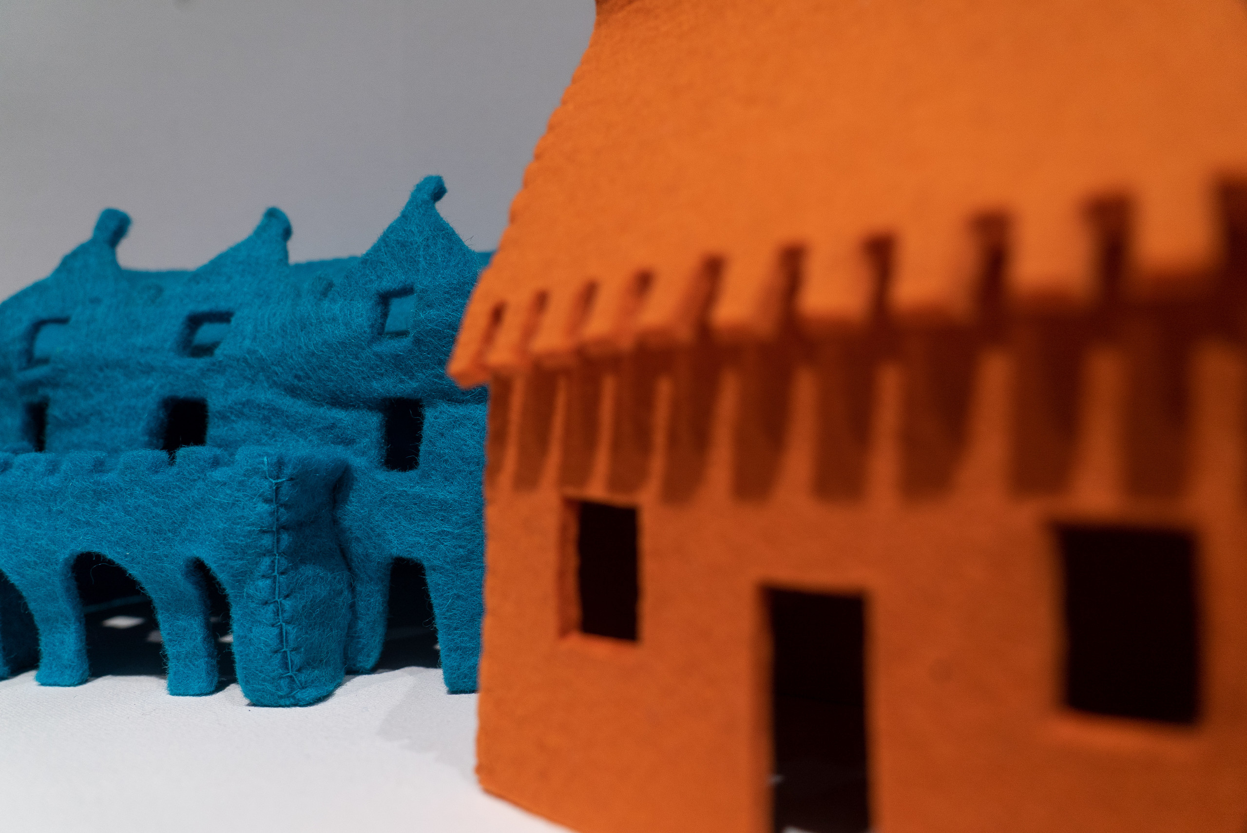 Close-up detail of a larger artwork features a view of two felt houses. On the viewer's right is an orange house that is out-of-focus while on the left is a blue house that is in-focus and has visible stitches, coarse texture, and rectangular windows.