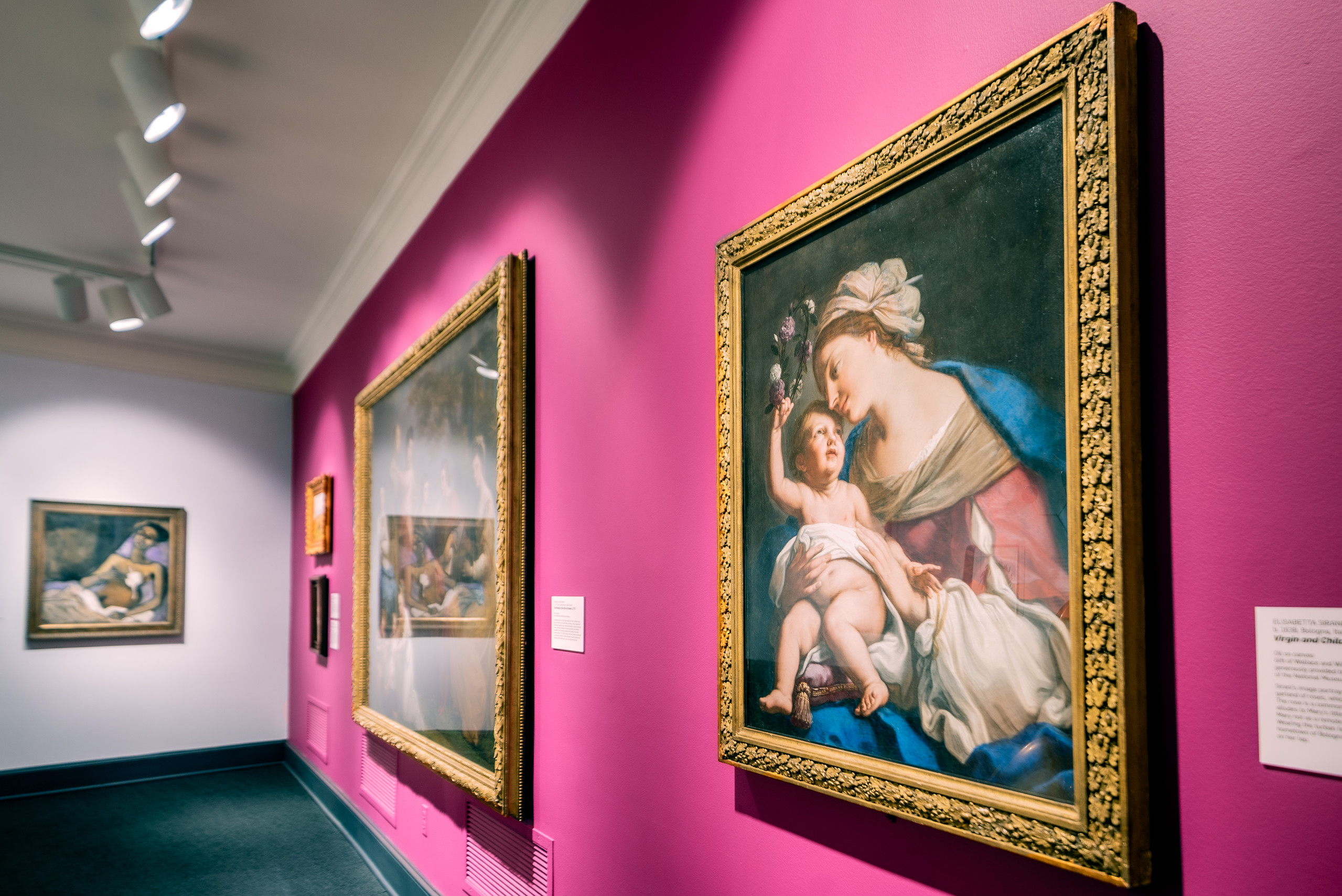 Oblique view of gallery with a Baroque painting of the Madonna and Child in a gilded frame on magenta wall at right. In the distance, three more framed works hang on the same wall. Painting on the adjacent white wall is of a reclining figure with a bandage on chest.