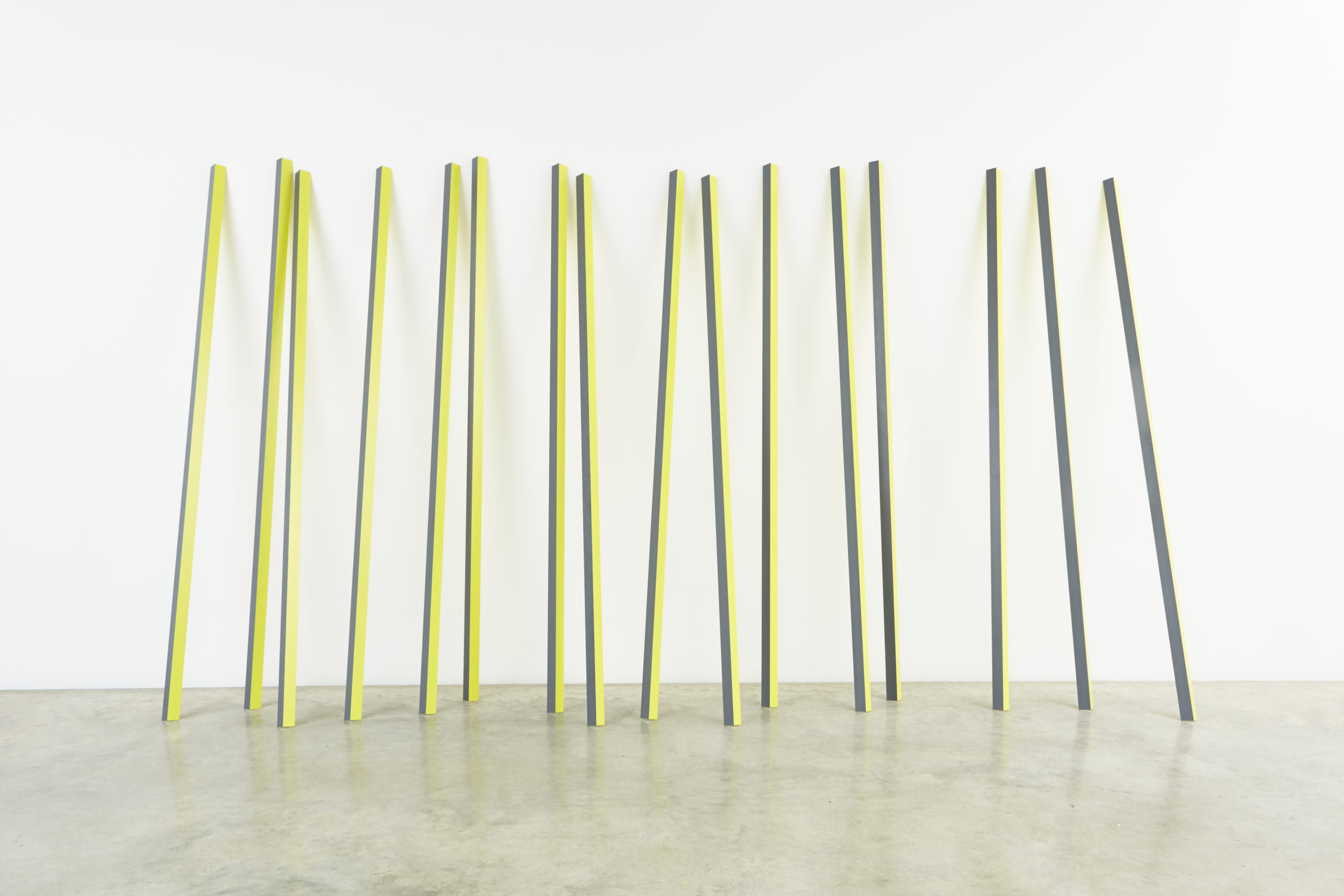 Sixteen rectangular yellow and grey aluminum poles lean up against a wall