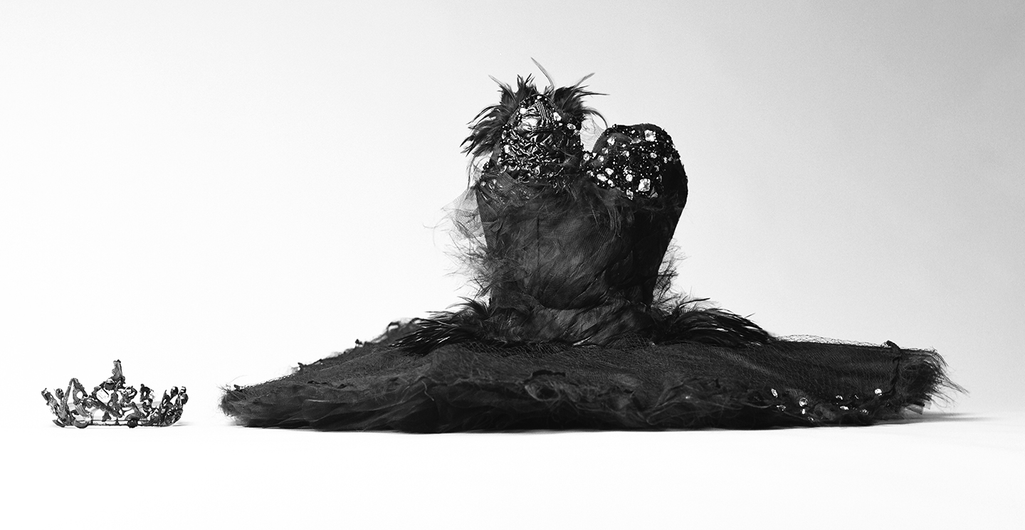Black feathered tutu rests on the ground against a white background. A dark tiara rests on the ground to the left of the dress.