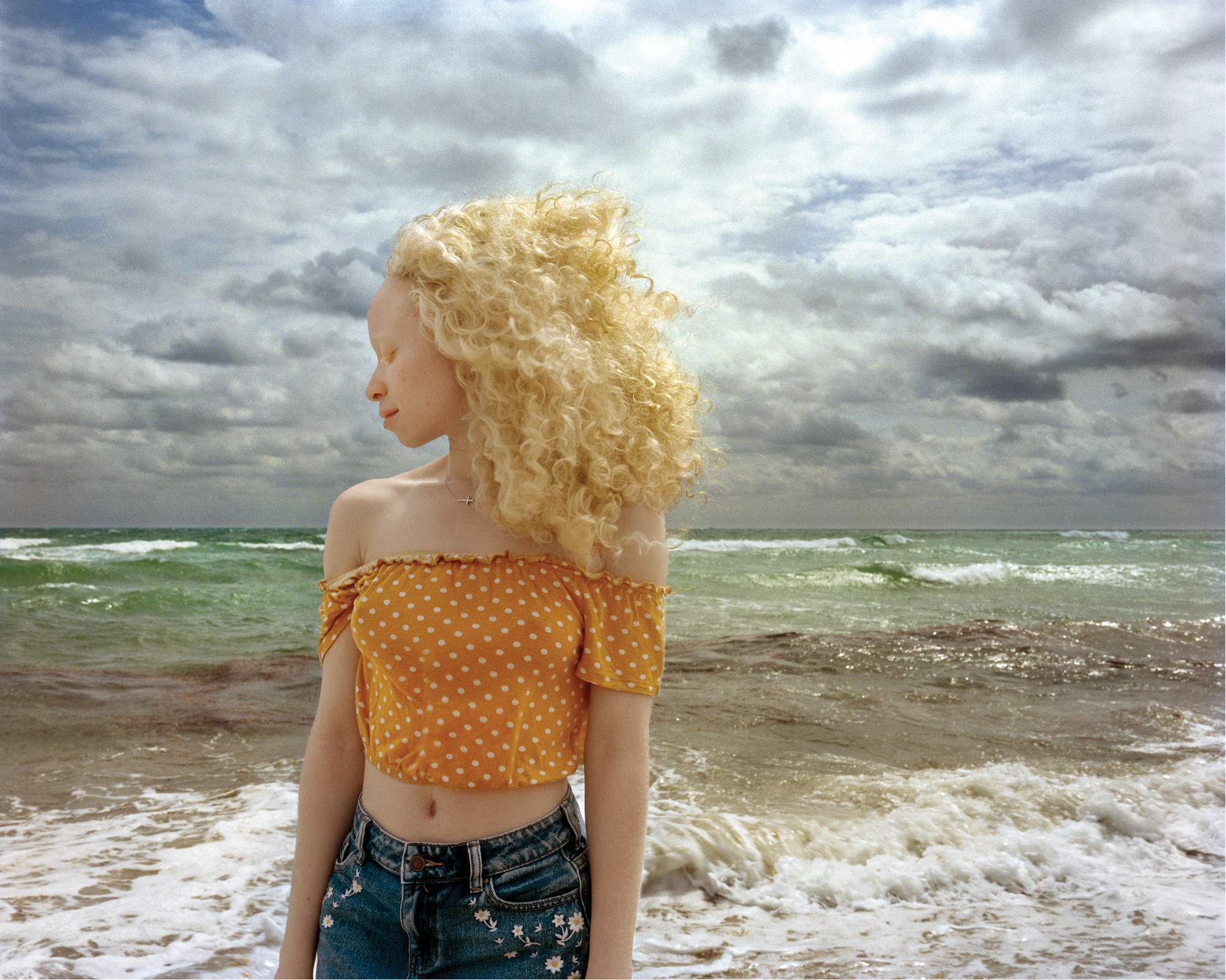 In front of a stormy ocean, a woman with light skin and blonde, wind-blown hair stands with head turned in profile and eyes closed.