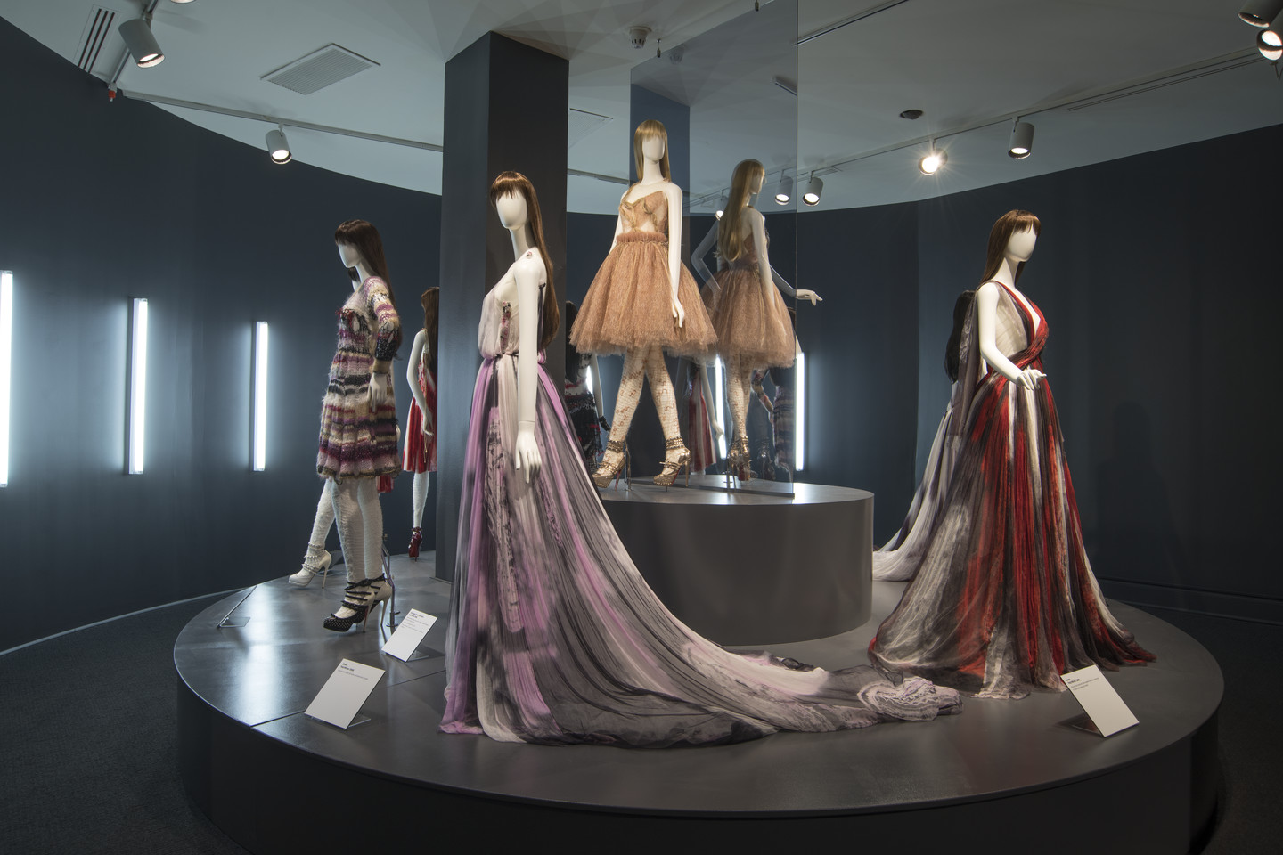 Four light skin mannequins display fashionable gowns of varying length on a circular platform.