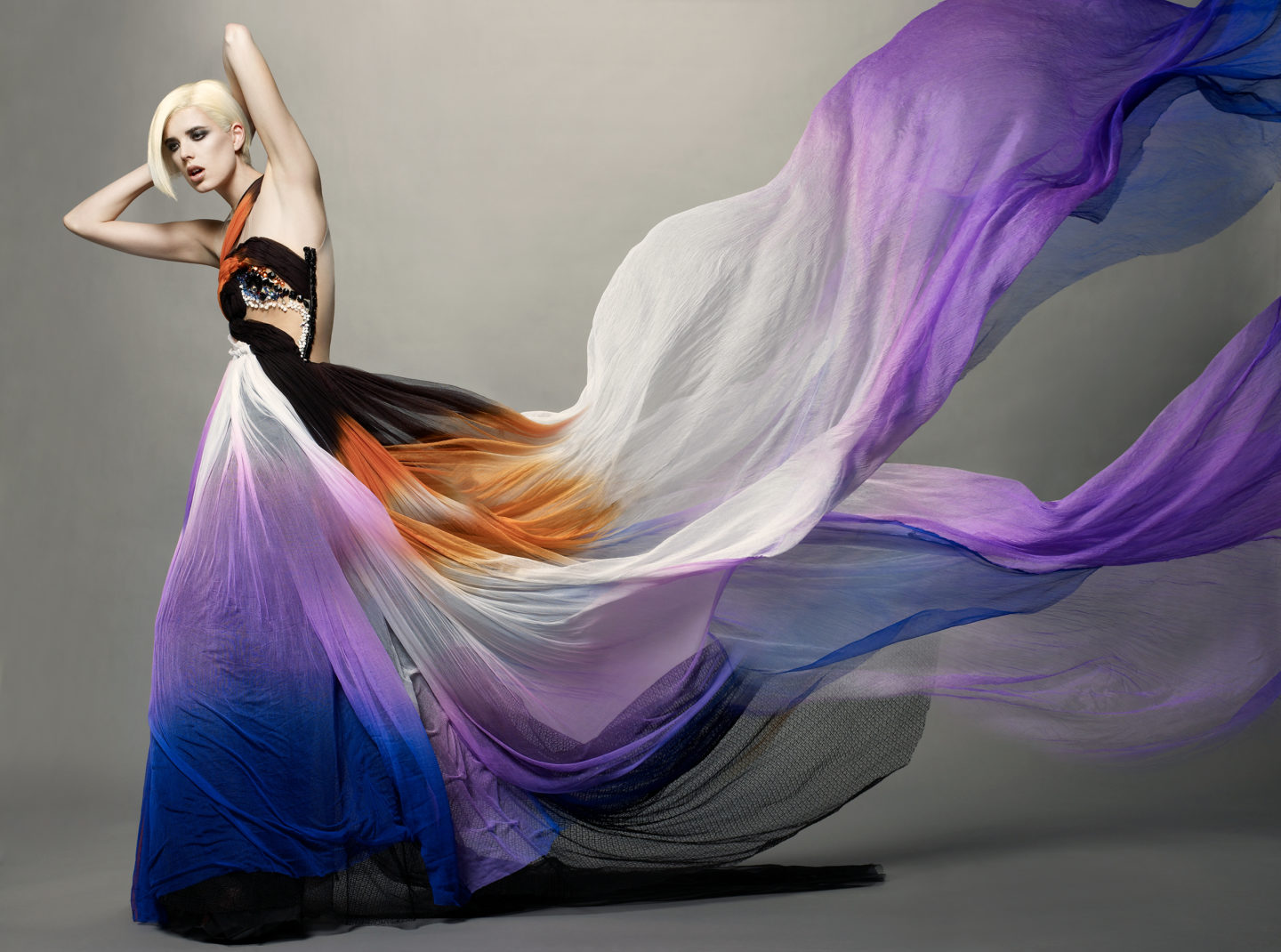 Model with light skin and platinum blond hair poses with hands behind her head wearing a long dress with shades of blue, purple, and orange. Train of dress dramatically flows off the right and top edge of the frame.