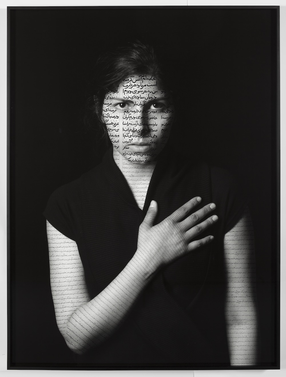 Black-and-white photograph of a woman with light skin and dark hair wearing a black t-shirt that blends into the dark black background. She holds her right hand over her heart and stares out at the viewer. Her face and arms are inscribed with calligraphic verses in Farsi.